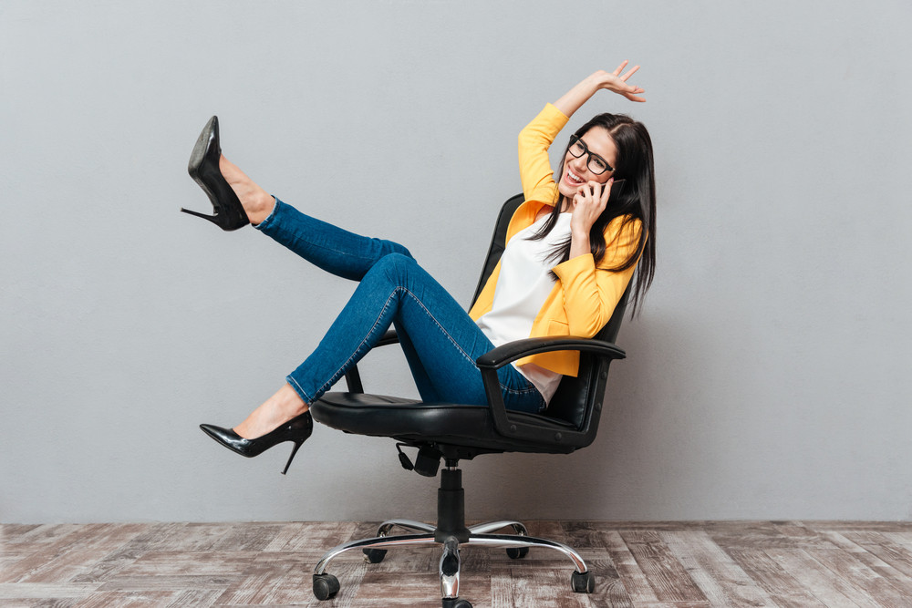Young pretty woman wearing eyeglasses and dressed in yellow jacket sitting on office chair while talking by phone over grey background.