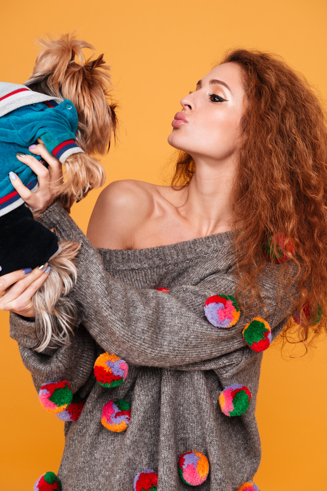 Young red hair woman kissing her yorkshire terrier isolated on orange background