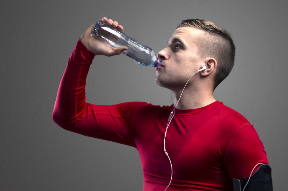 Young runner drinking water. Studio shot on a gray background.