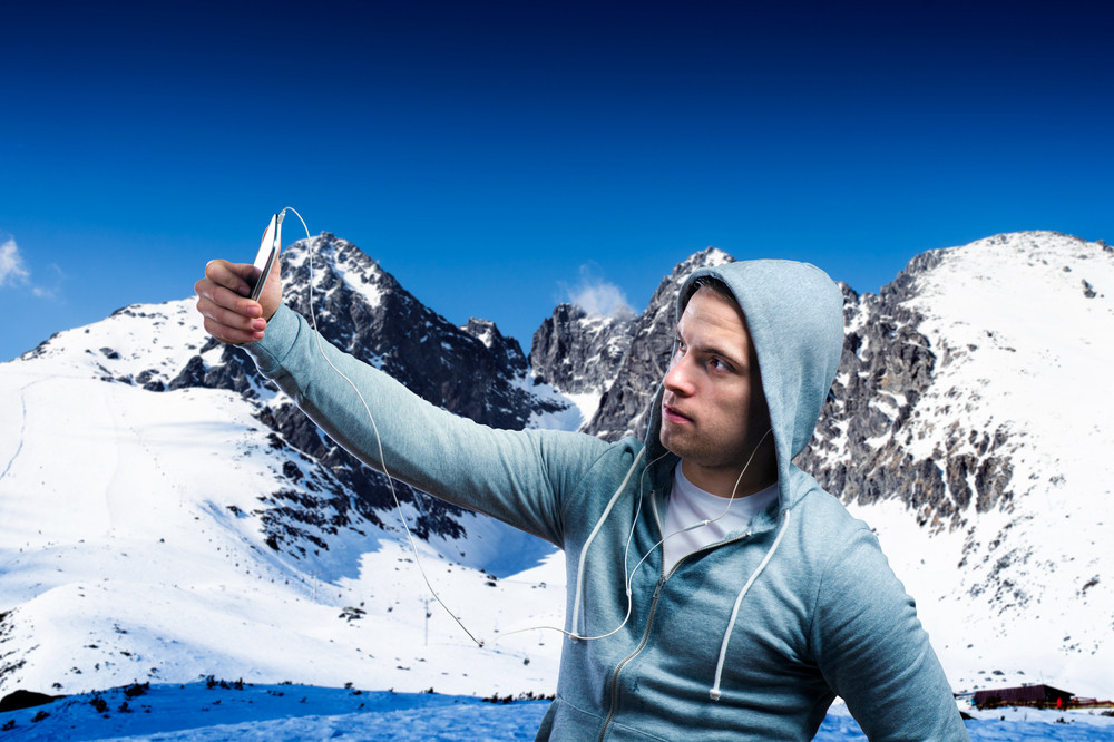 Young runner taking selfie in sunny winter mountains