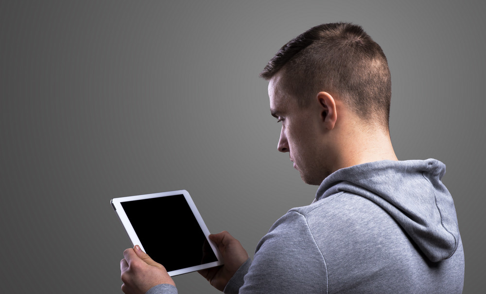 Young runner with a tablet. Studio shot on gray background.