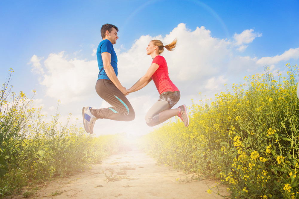 Young runners jumping outside in spring canola field