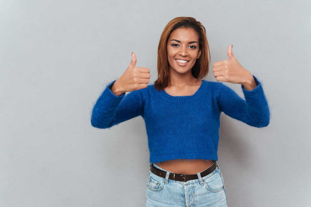 Young smiling african woman in sweater showing thumbs up and looking at camera. Isolated gray background