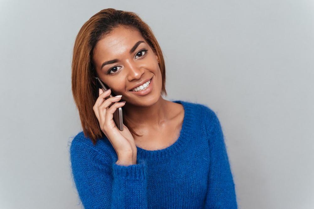 Young smiling african woman in sweater talking at phone and looking at camera. Isolated gray background