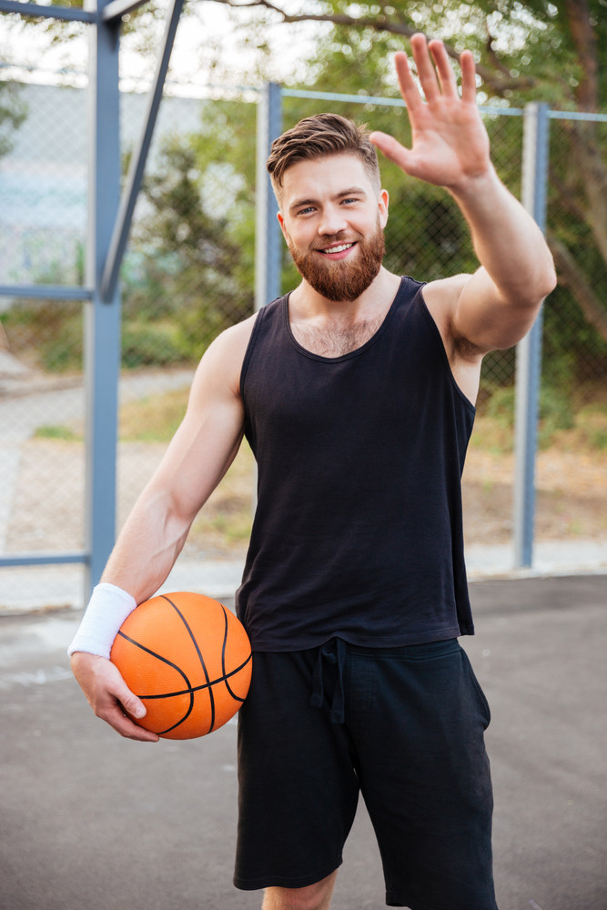 Young smiling bearded basketball player greeting somebody with hand waving outdoors