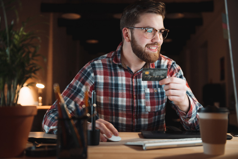 Young smiling businessman with computer and credit card shopping online in office