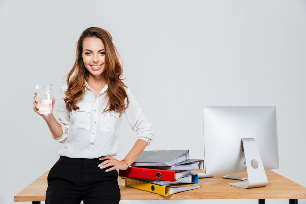 Young smiling businesswoman holding glass of water while standing at the office desk