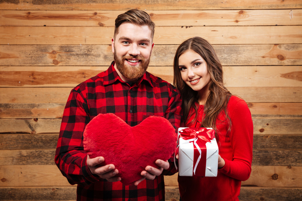 Young smiling casual couple holding presents and celebrating christmas isolated on a wooden background