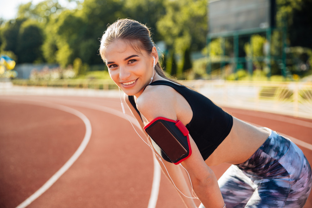 Young smiling cheerful female athlete ready to start running at the stadium track