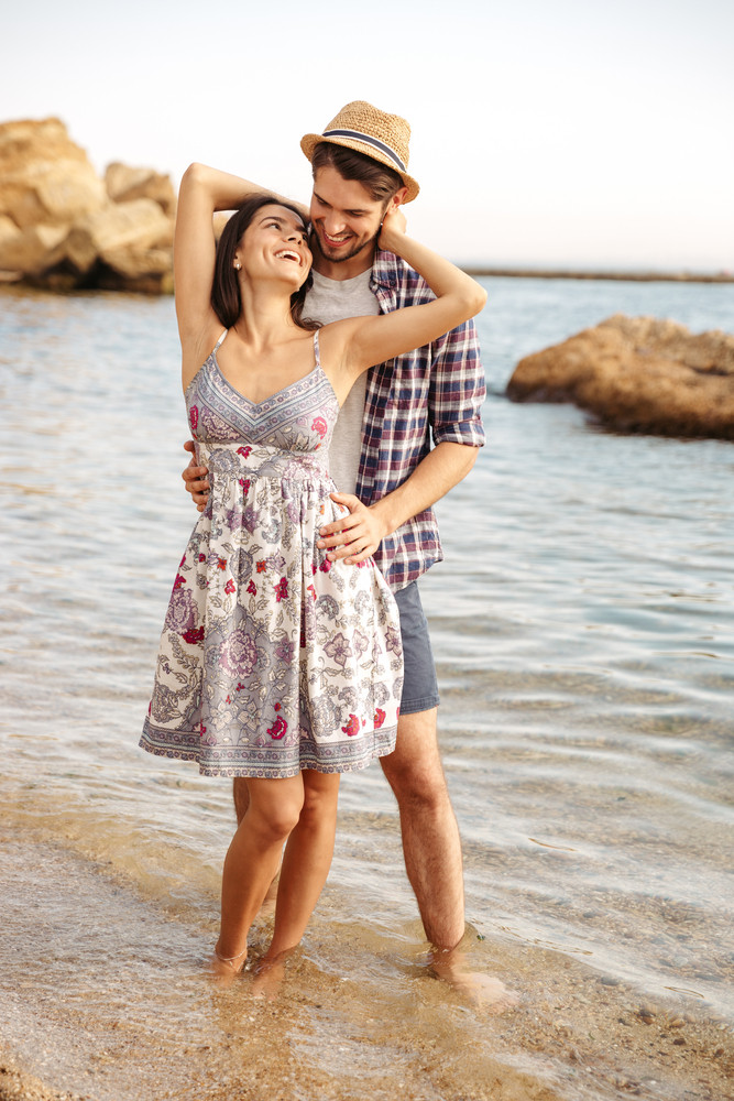 Young smiling couple in love standing at the beach and hugging