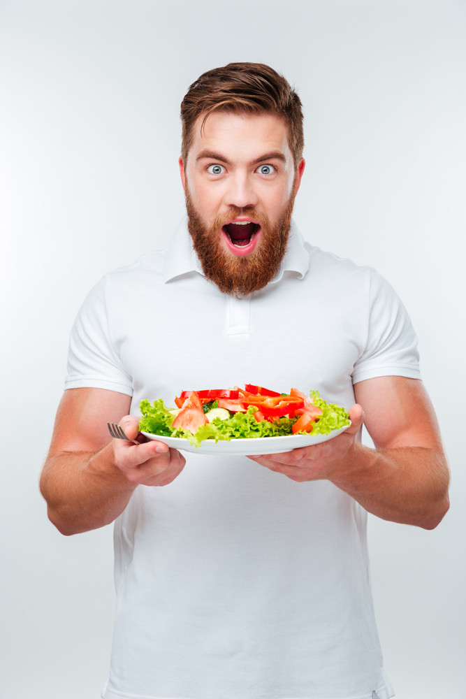 Young smiling man holding fork to eat fresh vegetable salad meal isolated on white background