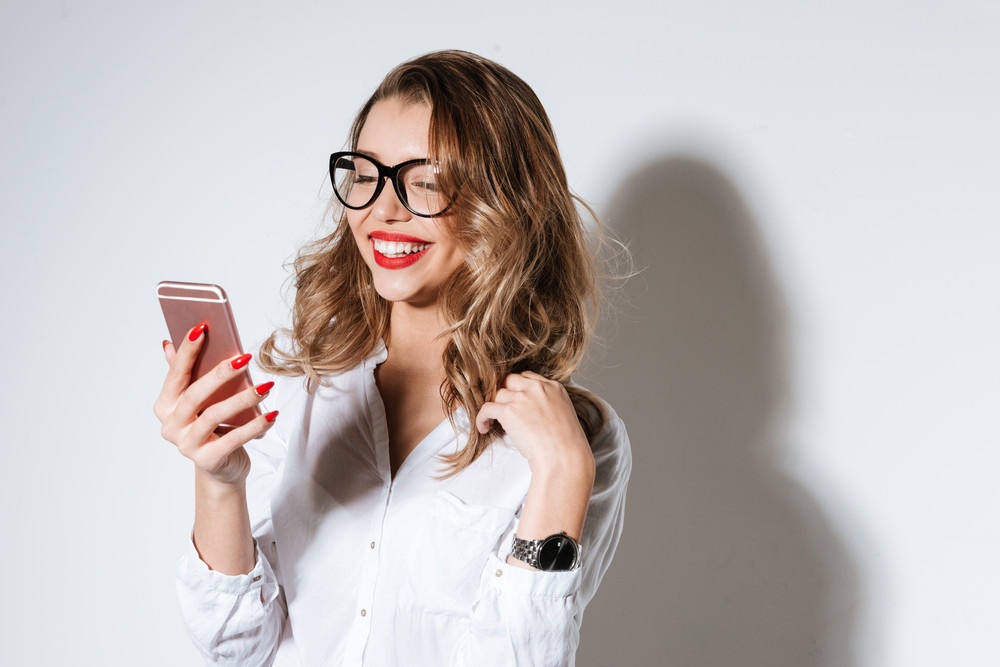 Young smiling woman in eyeglasses using smartphone over white background
