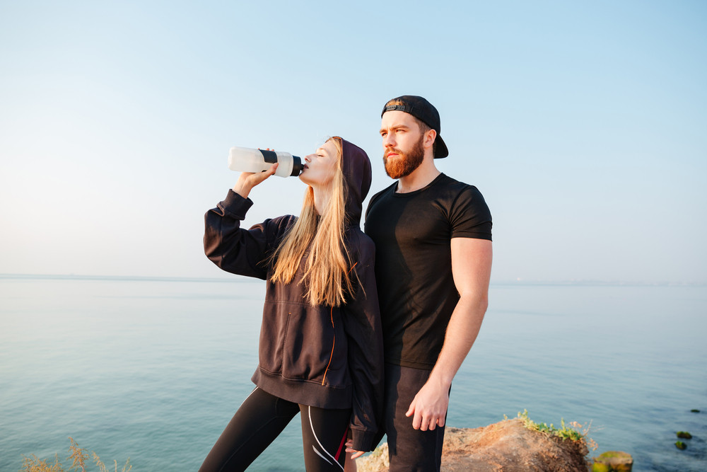 Young sports man and woman resting with water bottle after jogging outdoors