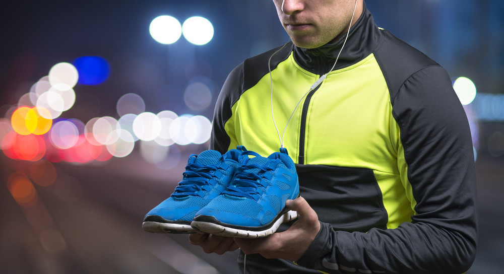 Young sportsman in the night city holding blue sneakers