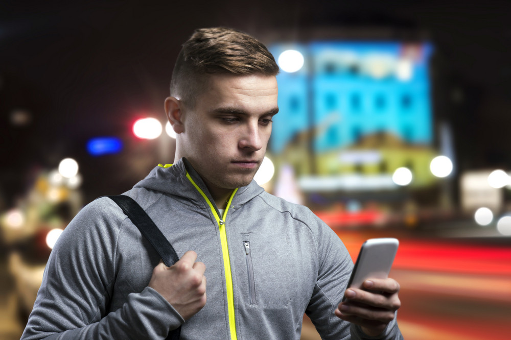 Young sportsman in the night city with smart phone