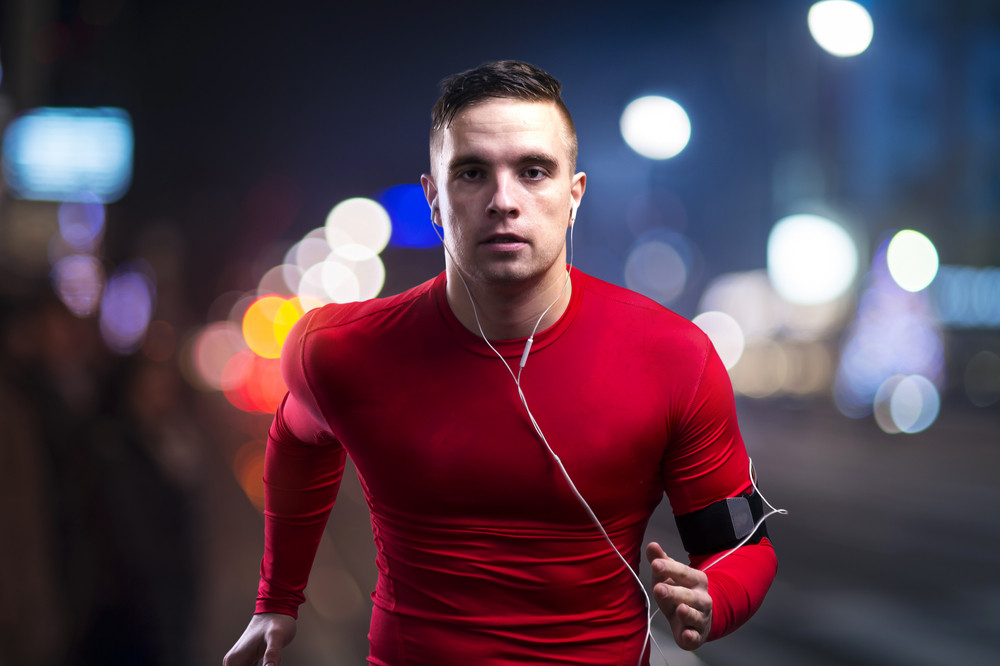 Young sportsman jogging in the night city