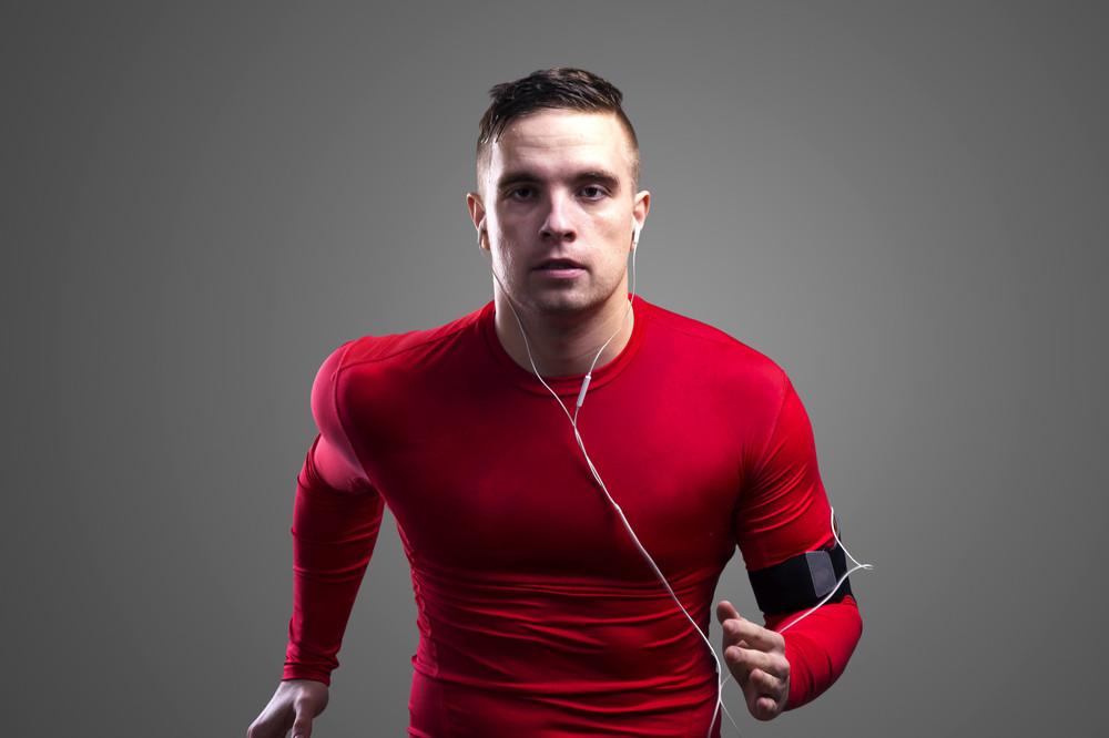 Young sportsman jogging. Studio shot on gray background.