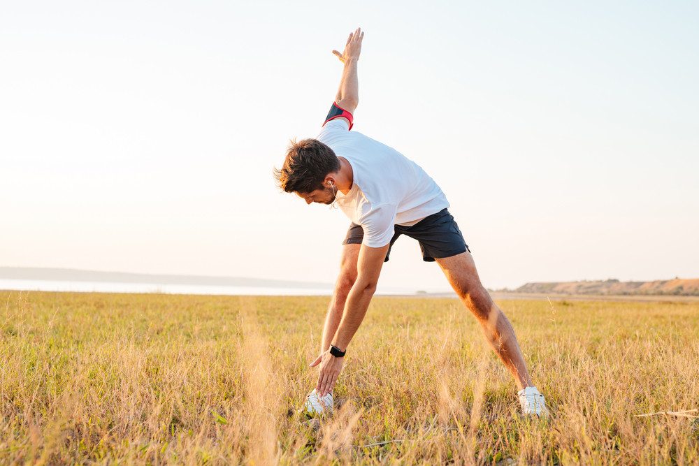 Young sportsman standing and stretching outdoors in the morning