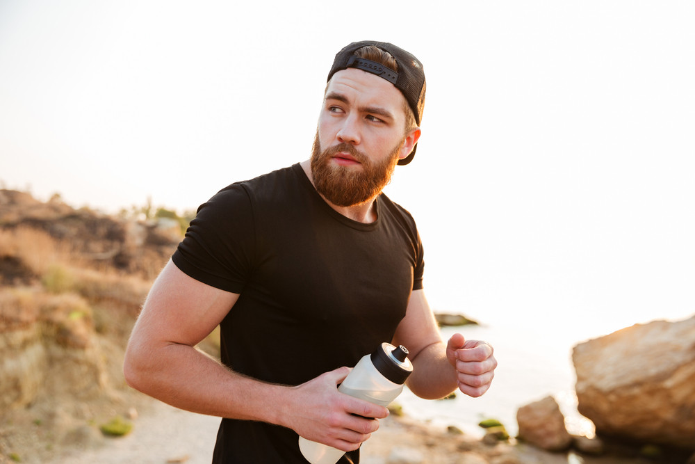 Young sporty bearded man athlete running at the rocky beach at the sunset