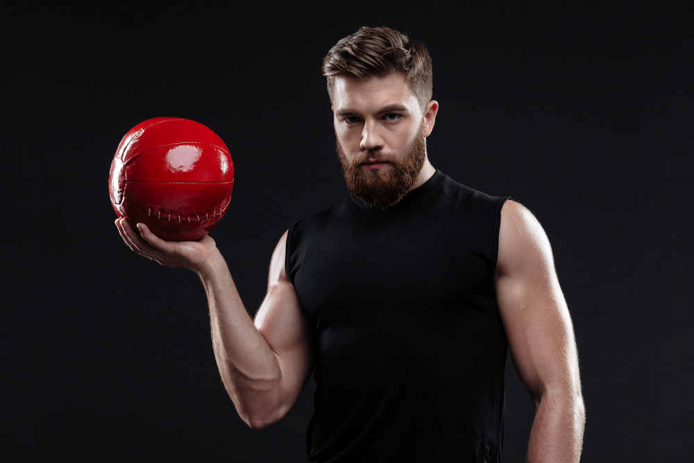Young strong man with ball. looking at camera. isolated dark background