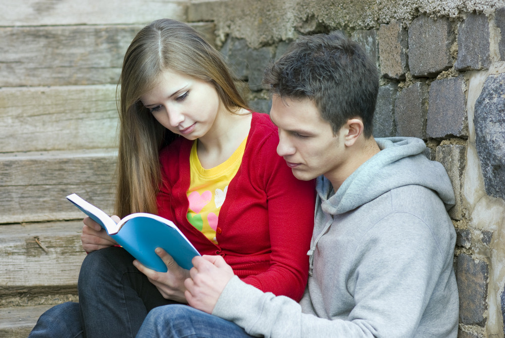 Young students are reading book together.