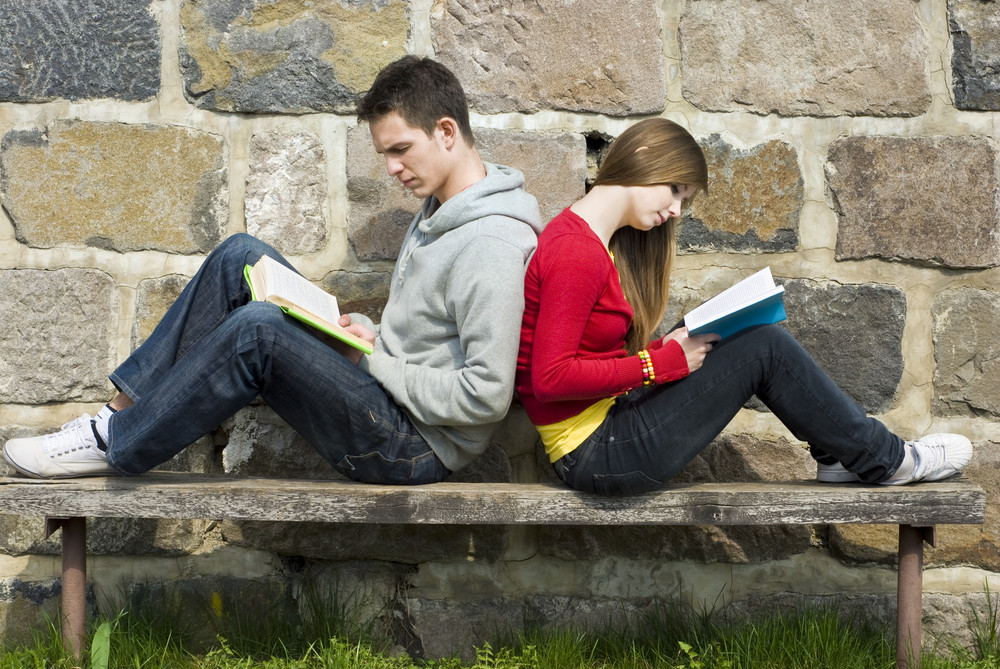 Young students are reading books together.