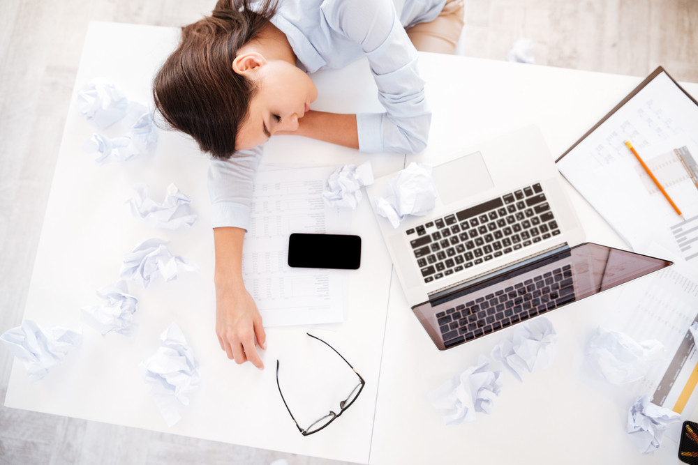 Young tired woman at office desk sleeping with eyes closed