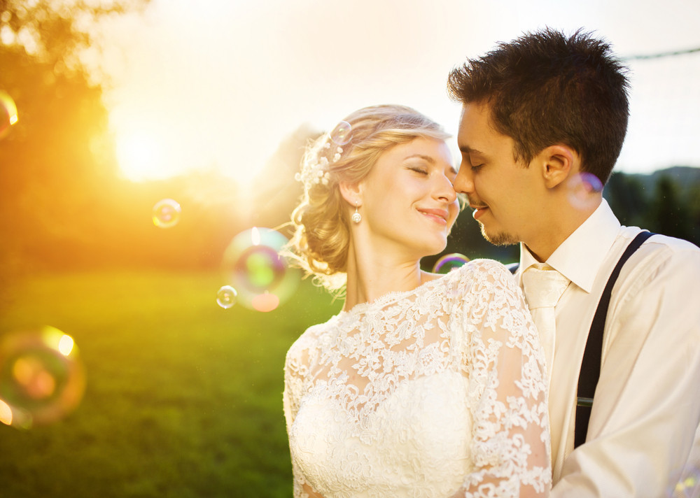 Young wedding couple enjoying romantic moments outside in a summer park.