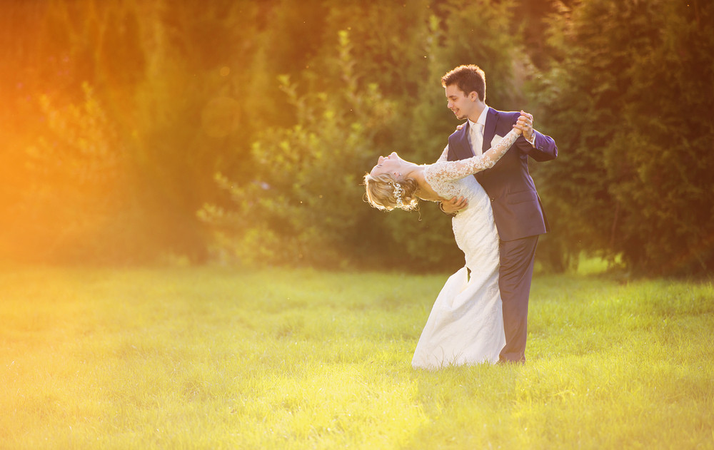 Young wedding couple enjoying romantic moments outside in summer park