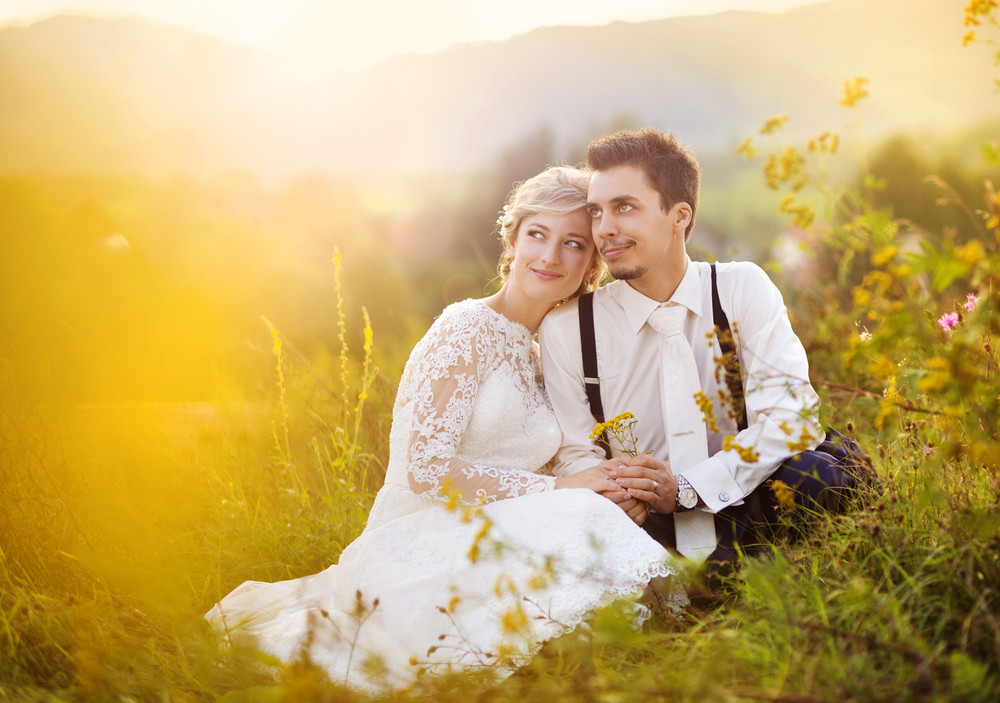 Young wedding couple enjoying romantic moments sitting on a meadow, summer nature outdoor