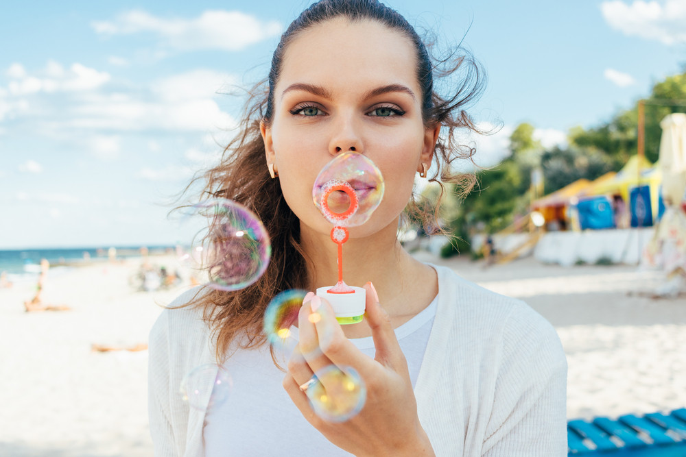 Young woman blow bubbles on the beach in the summer