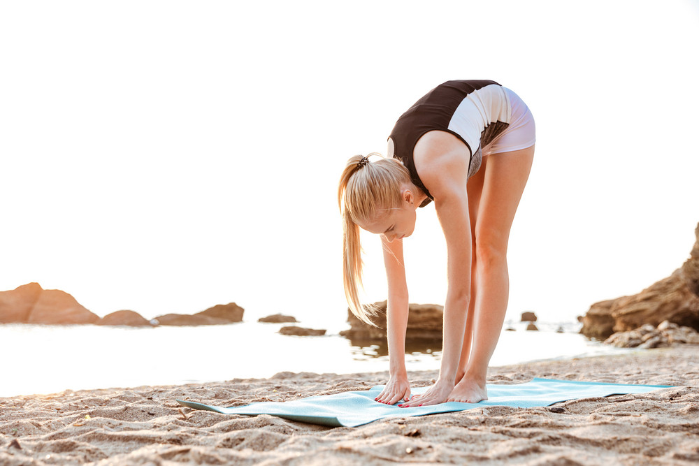 Young woman doing yoga exercises on mat outdoors in the morning