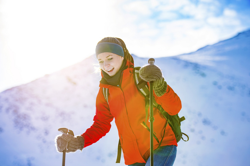 Young woman hiking outside in sunny winter mountains
