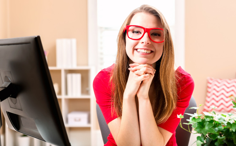 Young woman in a red dress working on computer