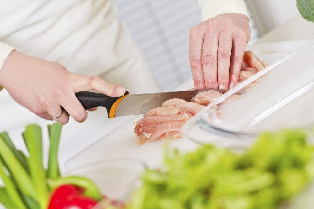 Young woman in a white kitchen chopping chicken meat fillet. Vegetable on the bench.