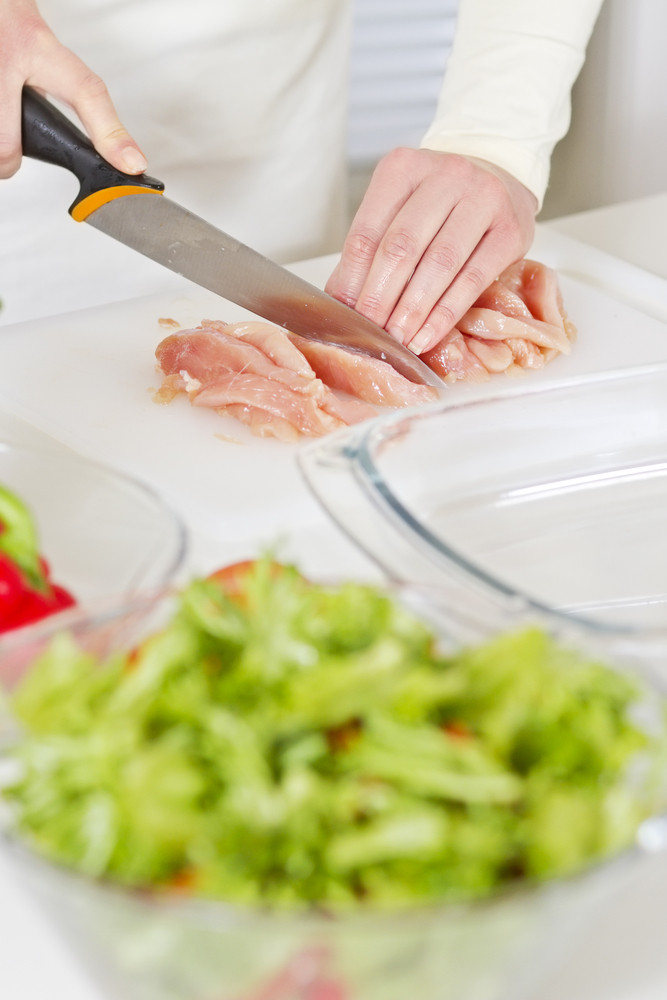 Young woman in a white kitchen cut chicken meat fillet. Vegetables.