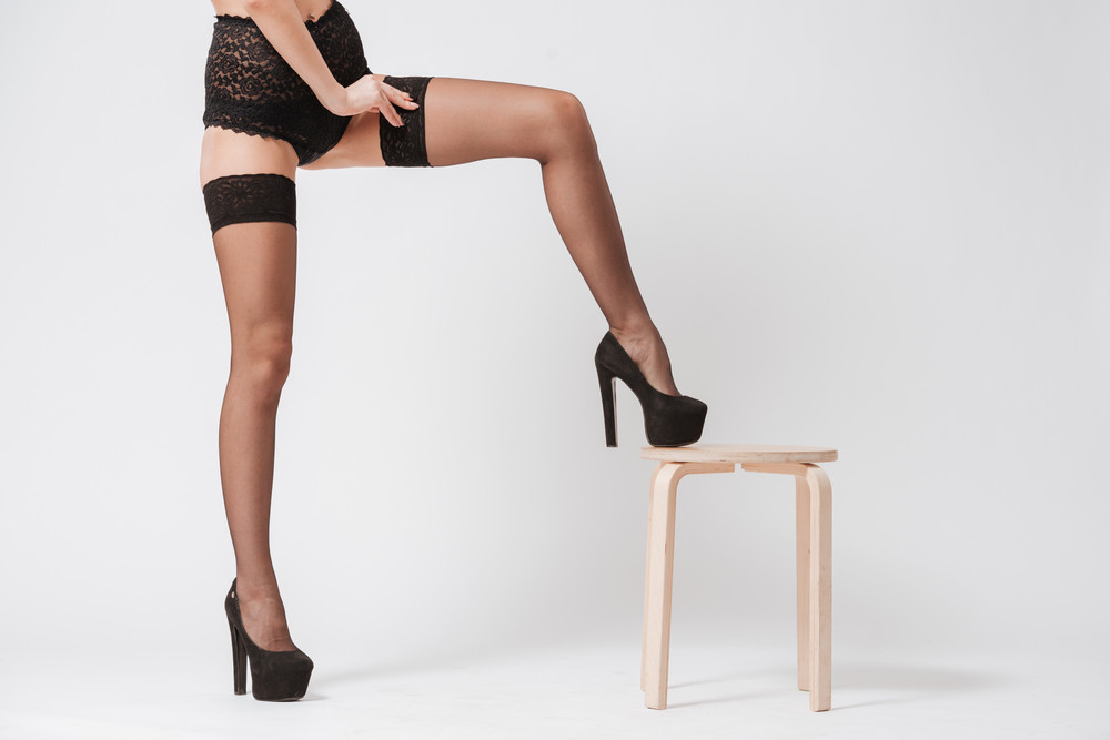 Young woman in black lingerie and stockings with leg in high heels on chair isolated on a white background