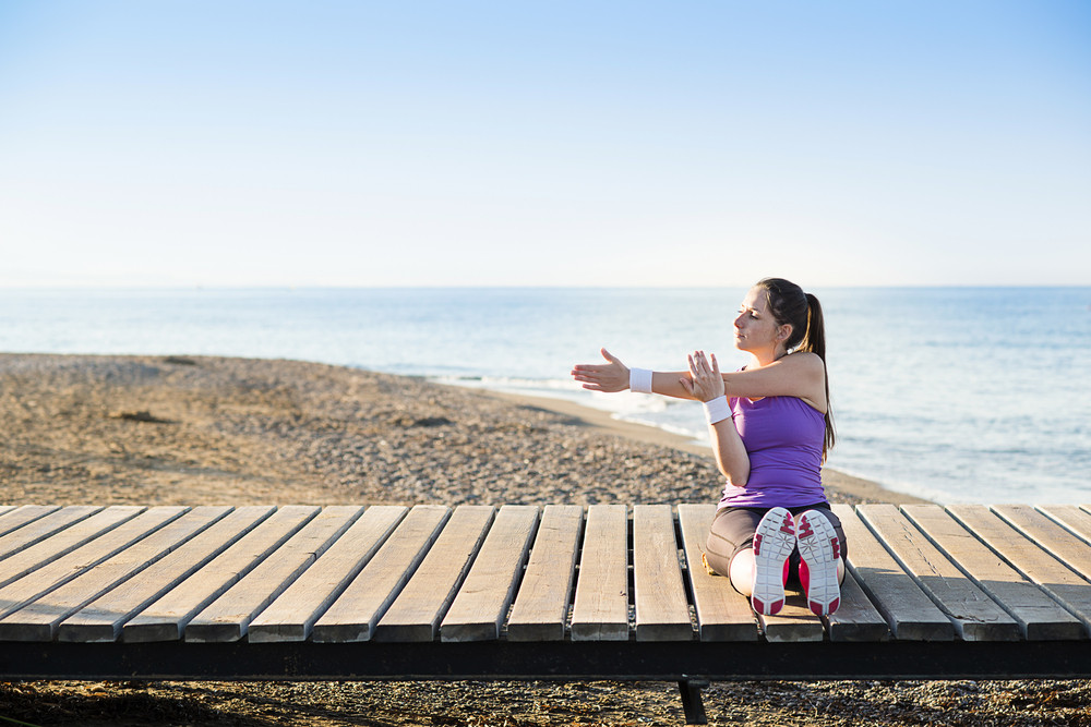 Young woman is doing exercises on pier close to the beach