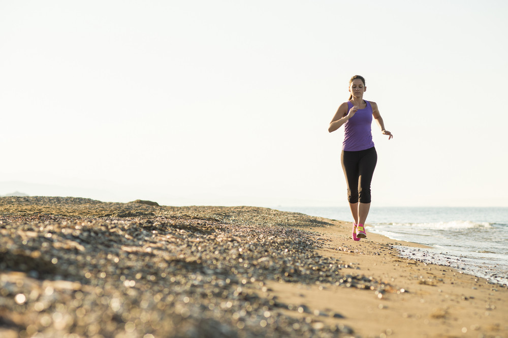 Young woman is running in sunny nature along the beach