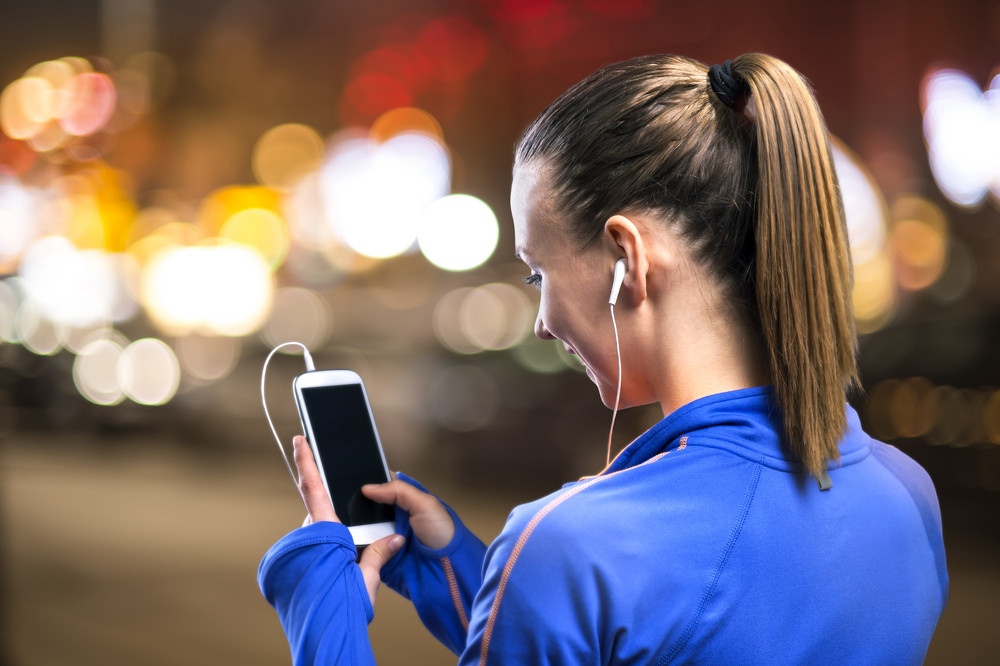 Young woman jogging at night in the city while listening music