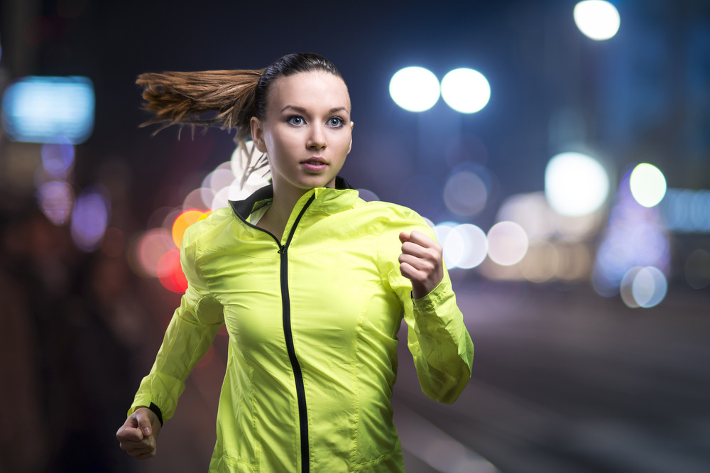 Young woman jogging at night in the city