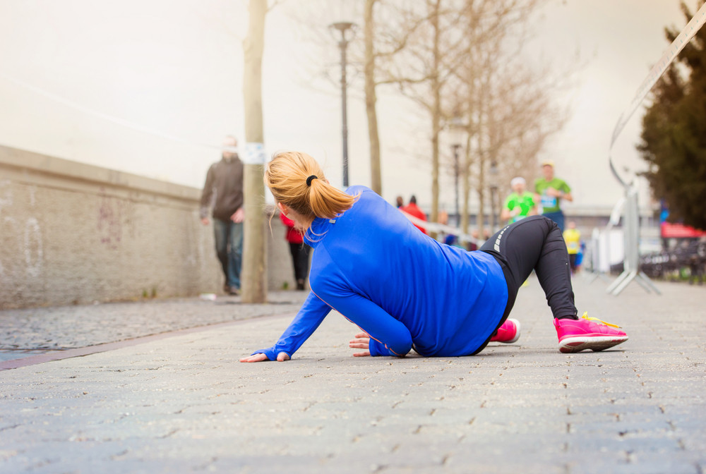 Young woman running in the city competition falling on the ground