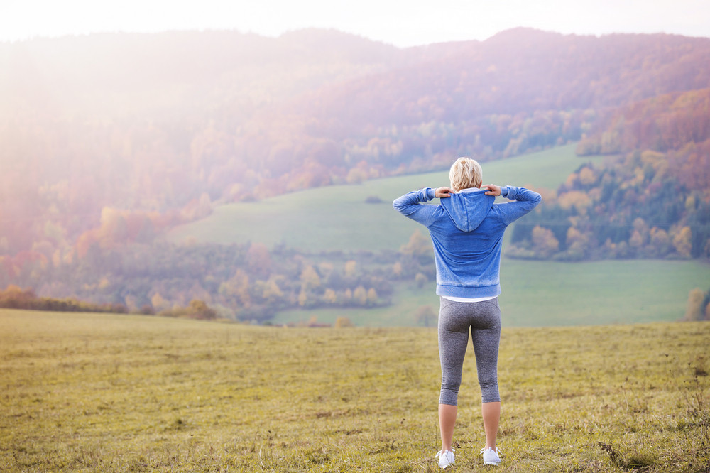 Young woman running outside in autumn nature