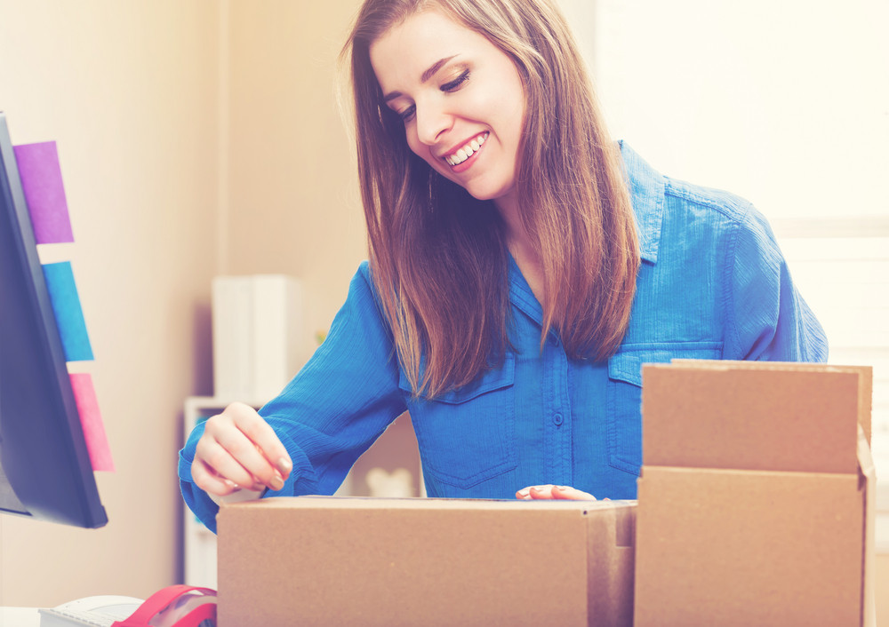 Young woman taping boxes to be shipped in her home office