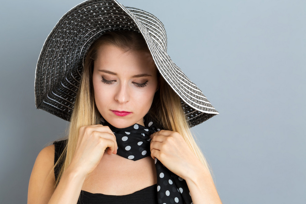 Young woman wearing a hat on a gray background