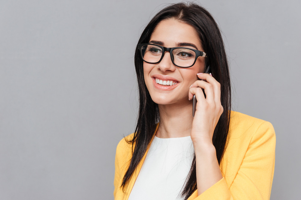 Young woman wearing eyeglasses and dressed in yellow jacket talking by her phone over grey background. Look aside.