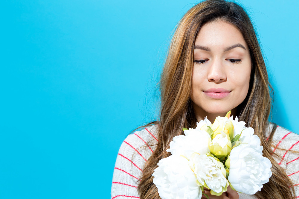 Young woman with white flowers on a blue background