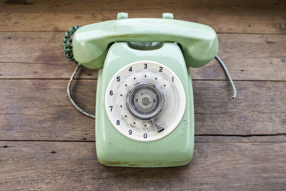 Green vintage telephone on brown wood desk background
