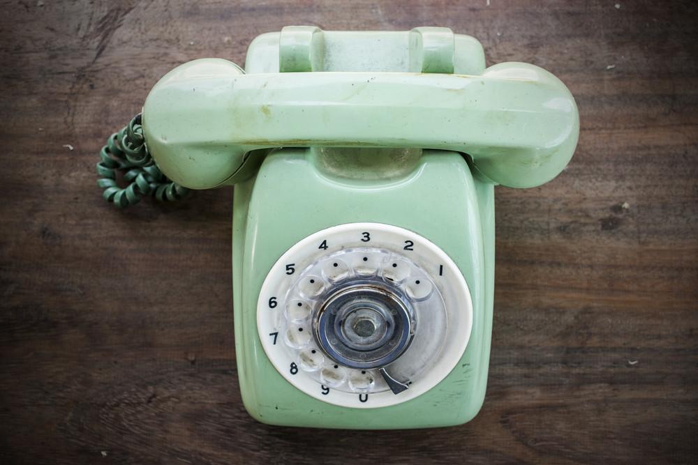 Green vintage telephone on brown wood desk background