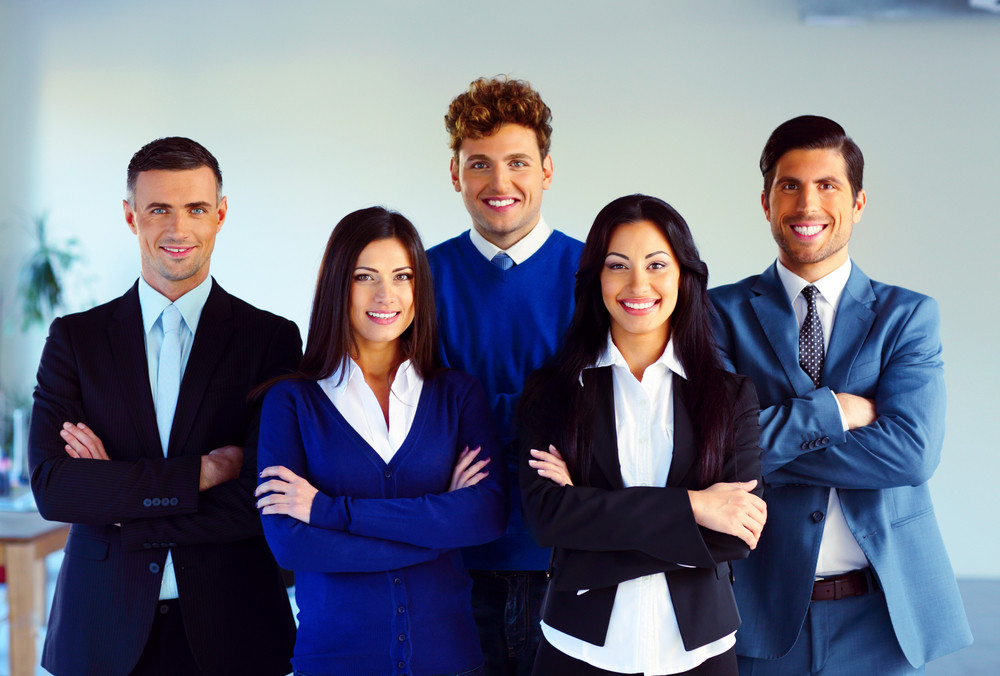 Group of a happy co-workers standing with arms folded in office